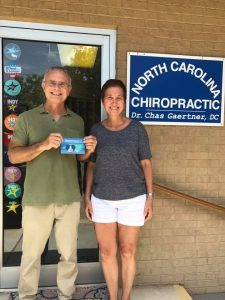 """NC Chiropractic owner with wife holding a """"Breastfeeding Welcome Here"""" sign in front of the store"""