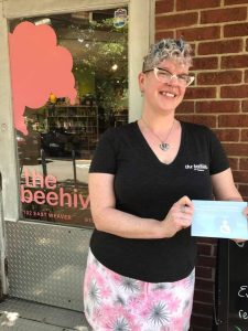 "The Beehive Salon employee holding ""Breastfeeding Welcome Here"" sign in front of store"