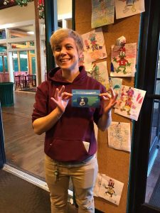 """Elmo's Diner employee smiling at the camera and holding the """"breastfeeding welcome here"""" sign"""
