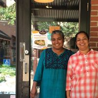 Two women are standing in front of Vimala's Curryblossom Café, smiling into the camera.