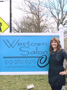 Hair stylist in front of Westown Salon sign