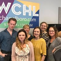 Six employees of WCHL, five women and one man, smiling into the camera with the WCHL logo behind them.
