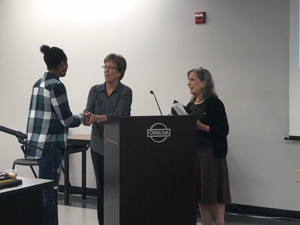 Carrboro Mayor is smiling and shaking hands with a breastfeeding family friendly communities supporter while another support holds the proclamation and looks on.