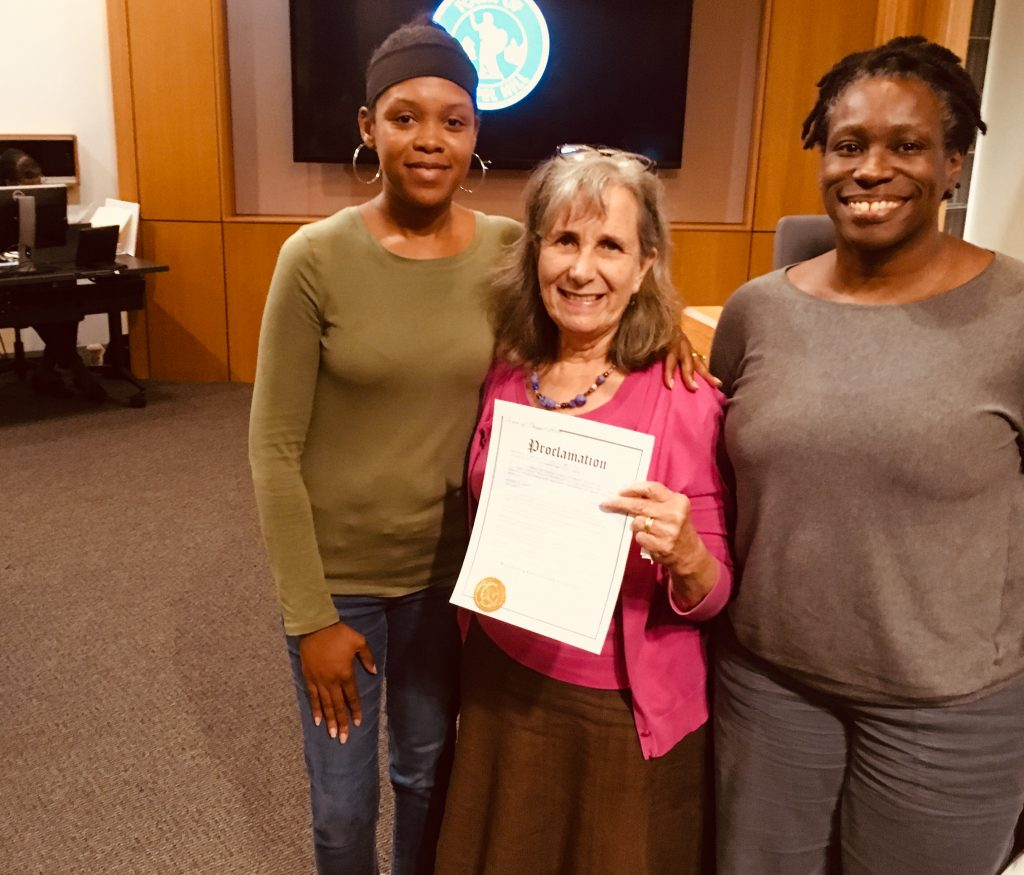 Town Council Member Donna Bell is smiling at the camera with two supporters of breastfeeding family friendly communities, the middle person is holding the proclamation