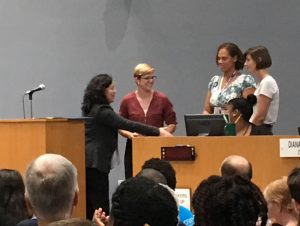 Durham Council Member smiling and facing three representatives of breastfeeding family friendly communities in Durham and presenting the three representatives with the breastfeeding family friendly communities proclamation.