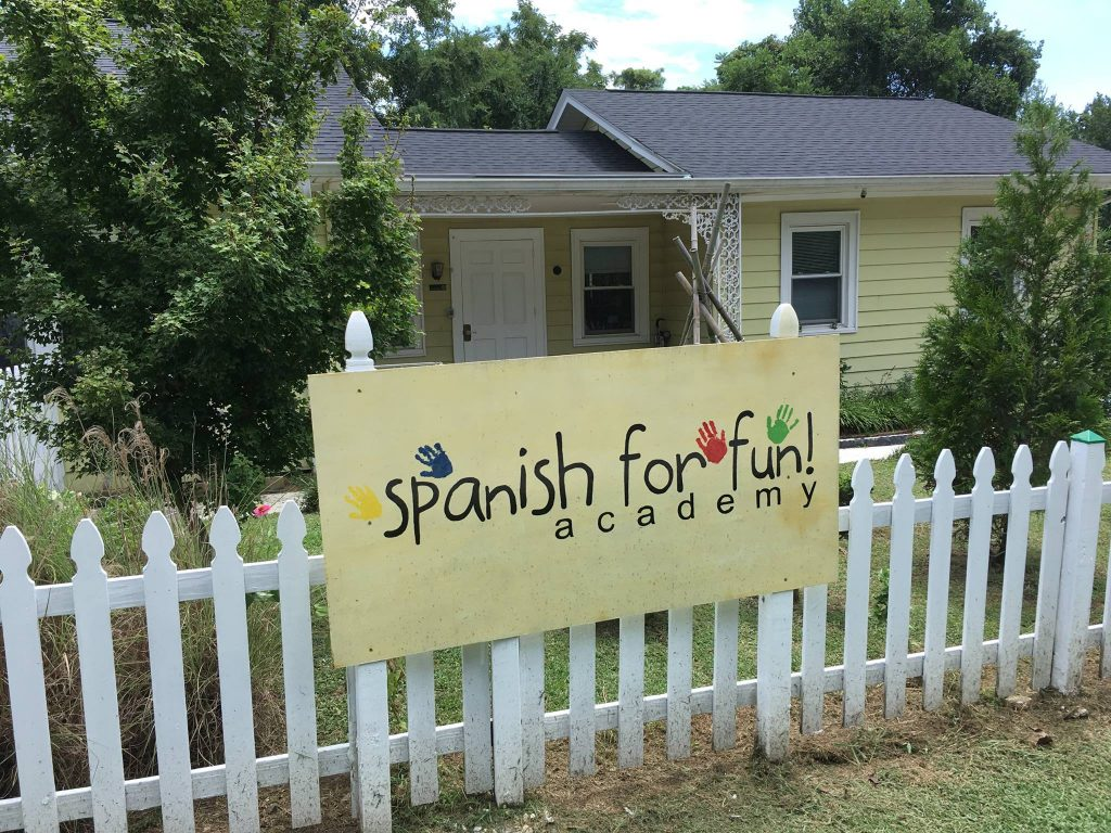 """Single story building with a door and two windows; a sign with the words """"Spanish for Fun academy"""" is on the picket fence that is in front of the building."""
